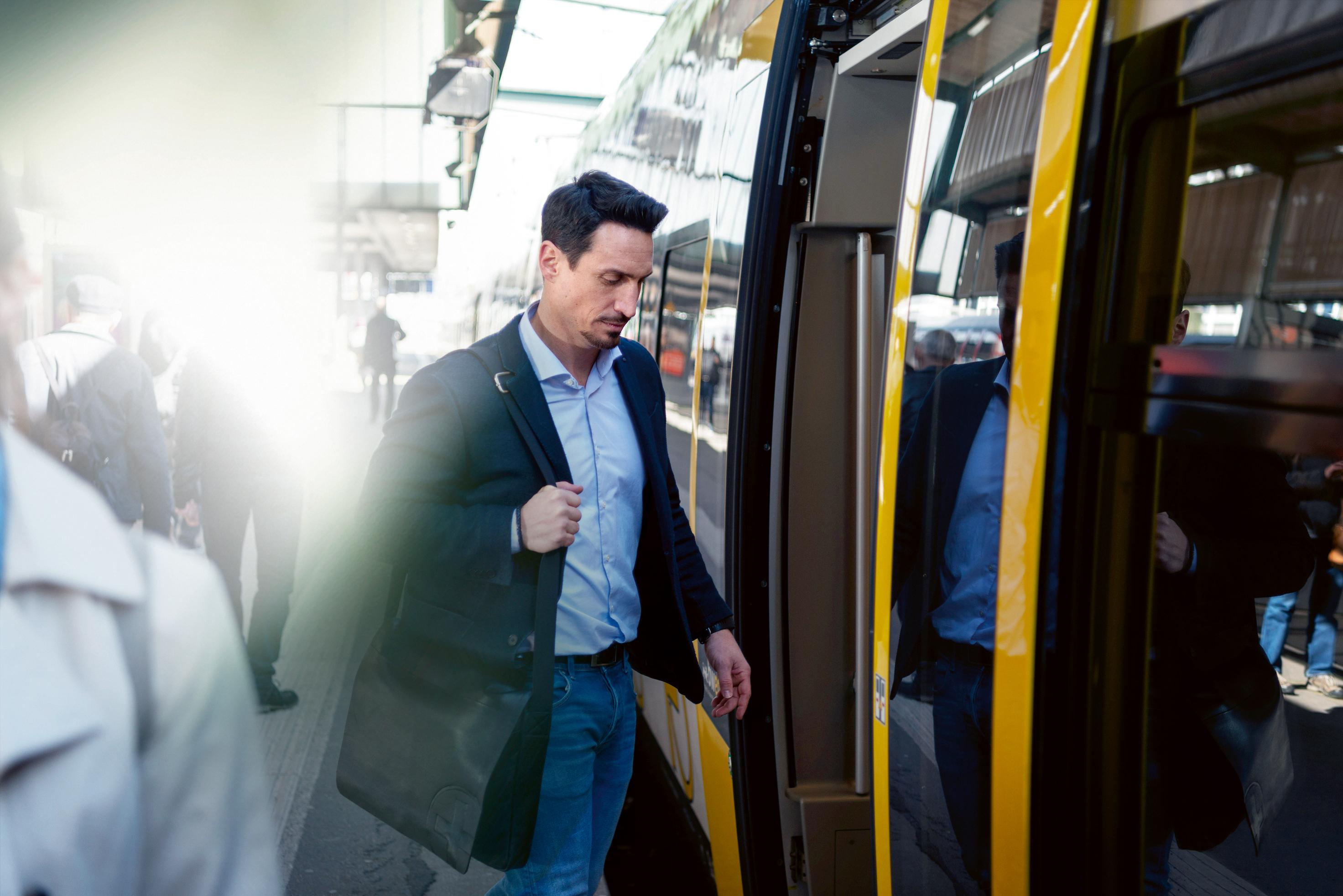 Mann steigt in den Zug